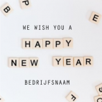 Nieuwjaarskaart met happy new year in scrabble stenen
